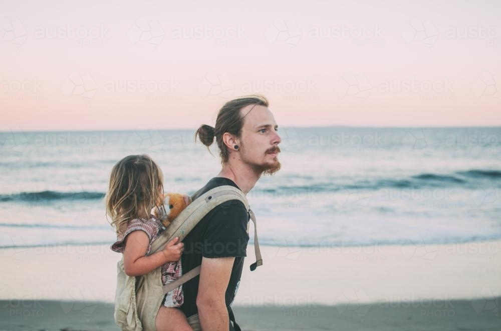 Man and child, baby wearing at the beach - Australian Stock Image