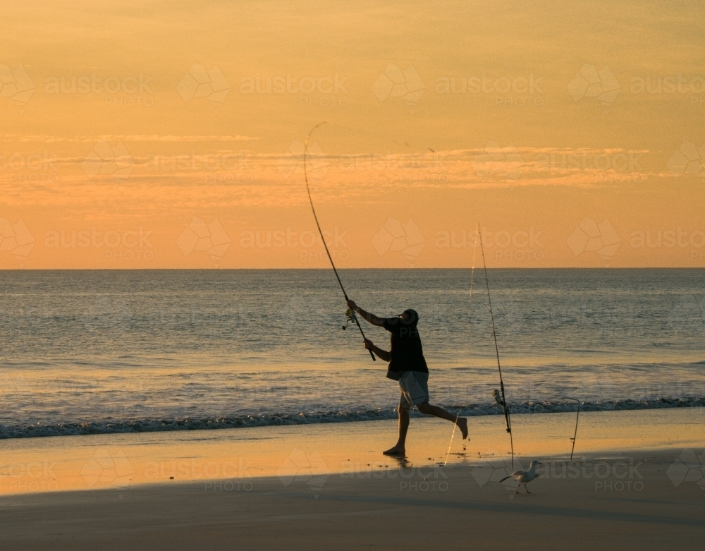 Man Casting a Surf Rod on Cable Beach at Dusk - Australian Stock Image