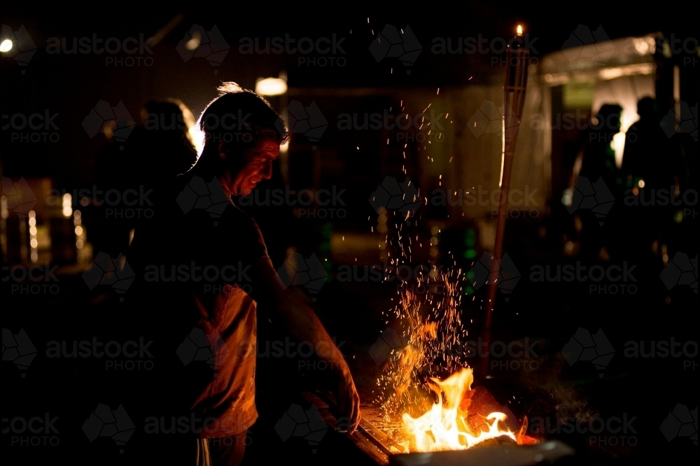Man cooking on a BBQ at night - Australian Stock Image