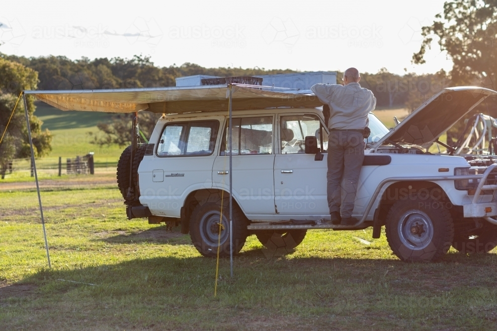 man doing work on old 4wd wagon with awning - Australian Stock Image