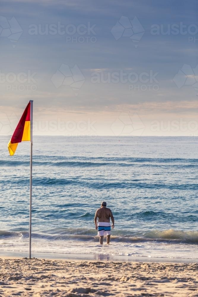 Man in board shorts facing the water beside surf life saving flag - Australian Stock Image