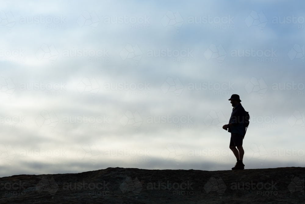 Man in silhouette against cloudy overcast sky - Australian Stock Image