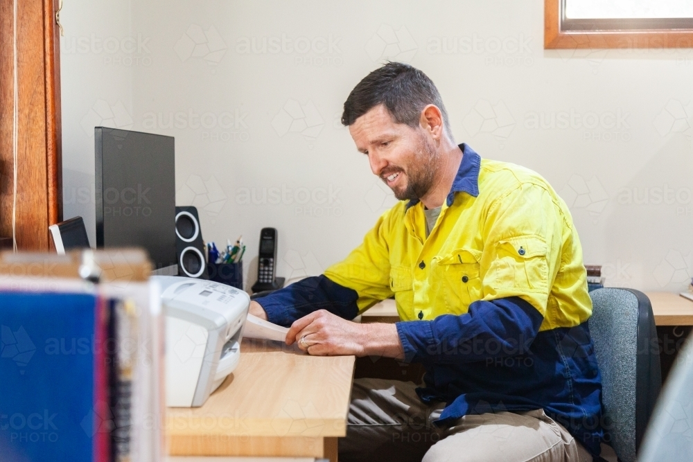 Man looking at paperwork in home office - Australian Stock Image