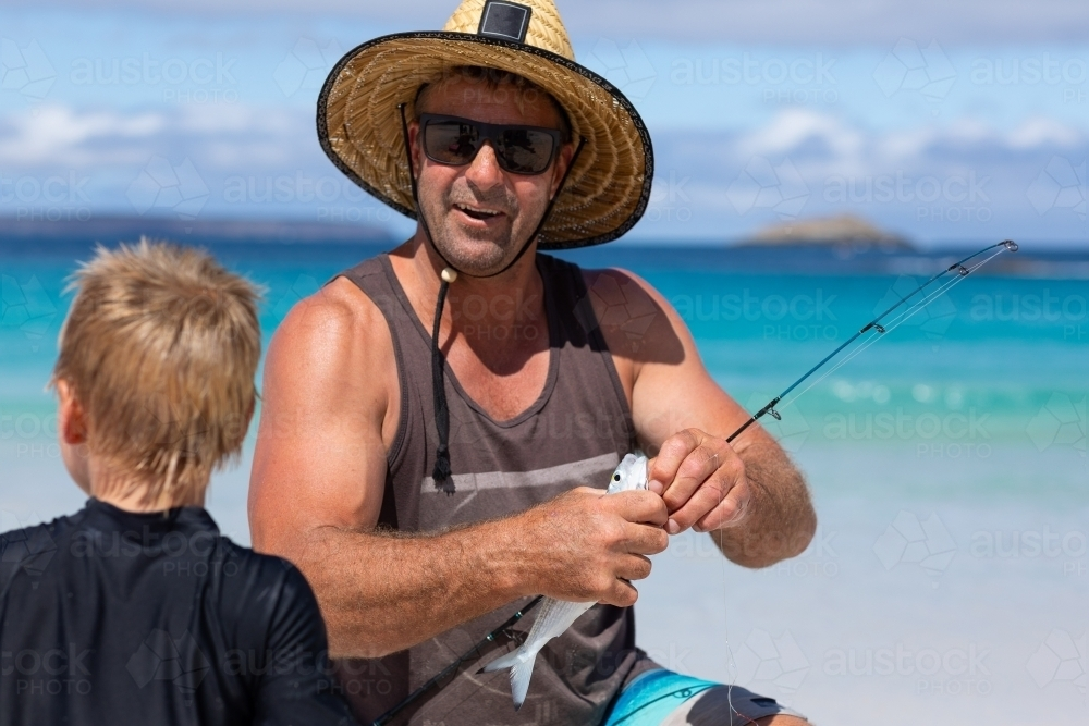 man on beach with young son putting bait on fishing hook - Australian Stock Image