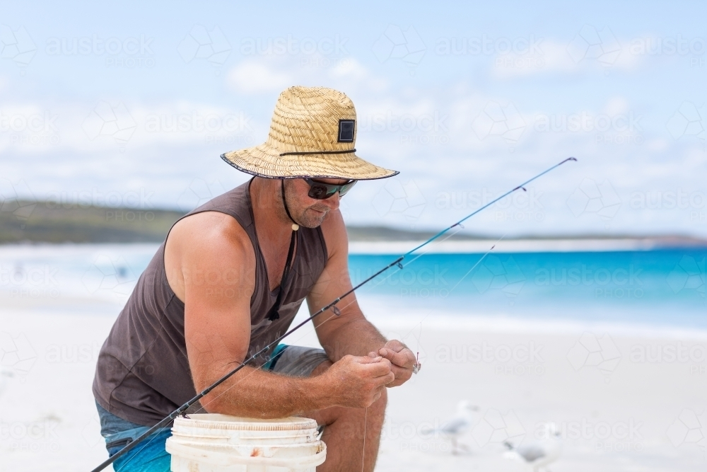 man on white sand beach kneeling down baiting fishing line - Australian Stock Image