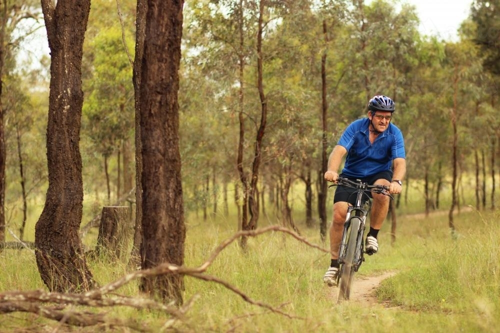 Man riding his pushbike on a dirt track among trees - Australian Stock Image