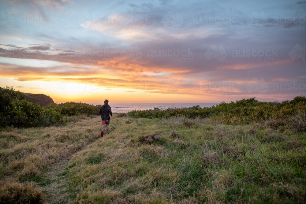Man Running Towards Beach at Sunrise - Australian Stock Image