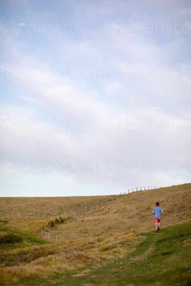 Man Running Uphill From Distance Under Blue Sky - Australian Stock Image