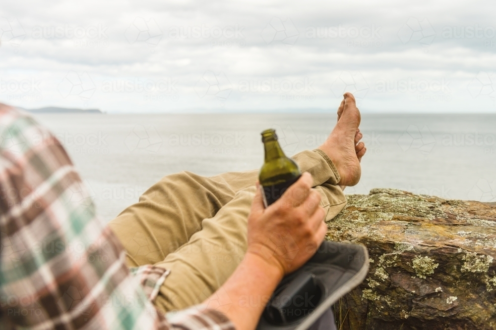 man sitting in tranquil camp spot by the ocean in his chair, with a beer - Australian Stock Image