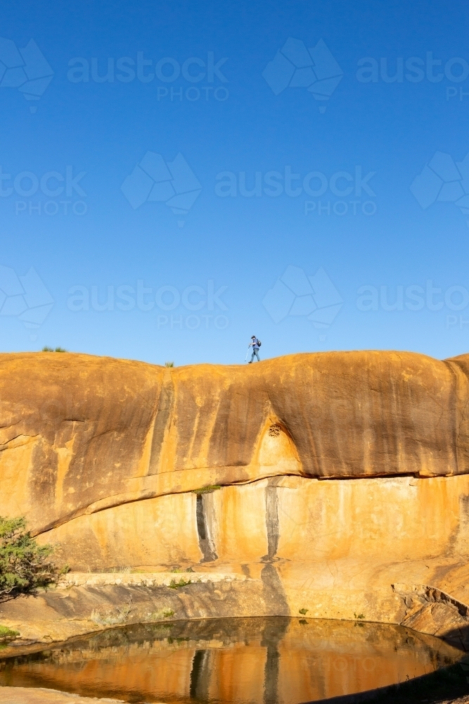 man walking across rock above a natural pool of water - Australian Stock Image