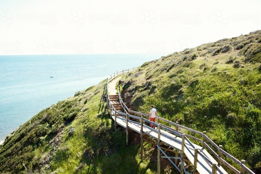 Man walking on a walkway over a mountain on the coast - Australian Stock Image