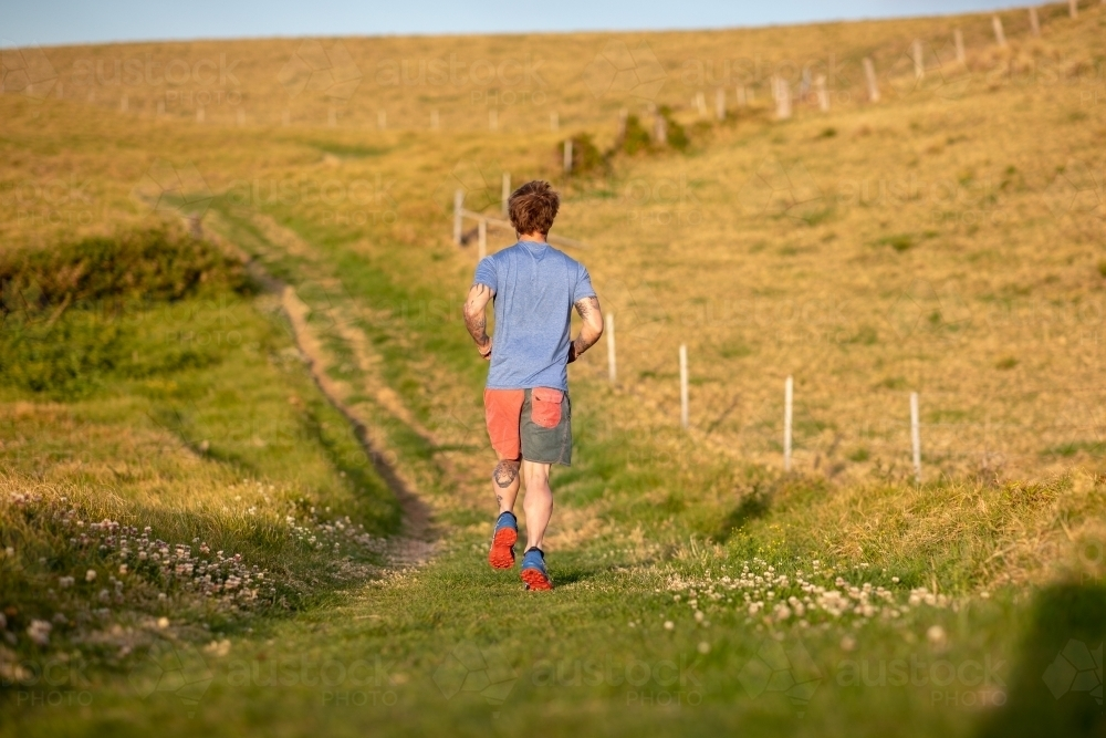 Man with Tattoo Running in Countryside - Australian Stock Image
