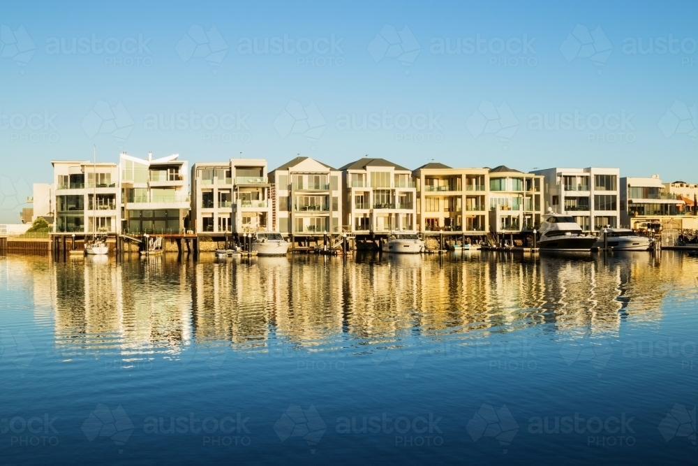 Marina homes reflecting in the water in morning light - Australian Stock Image