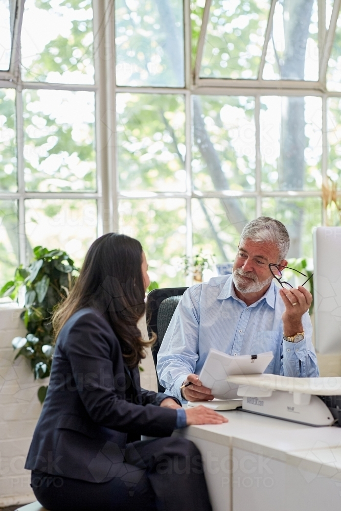 Mature aged male office worker meeting with a woman in a creative warehouse space - Australian Stock Image
