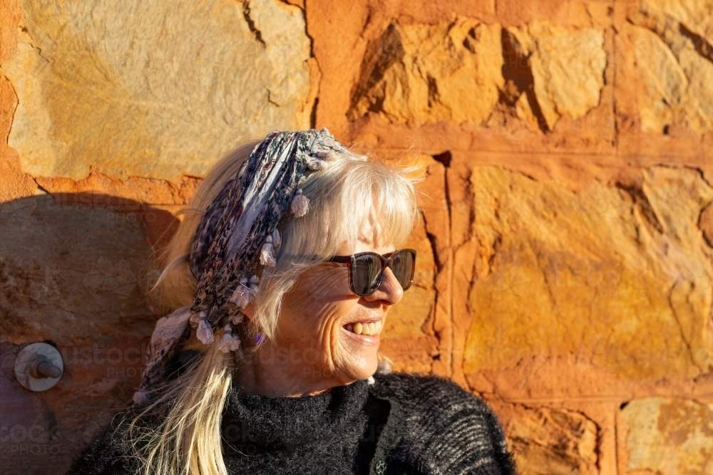 Mature woman head and shoulders against sunlit stone wall - Australian Stock Image