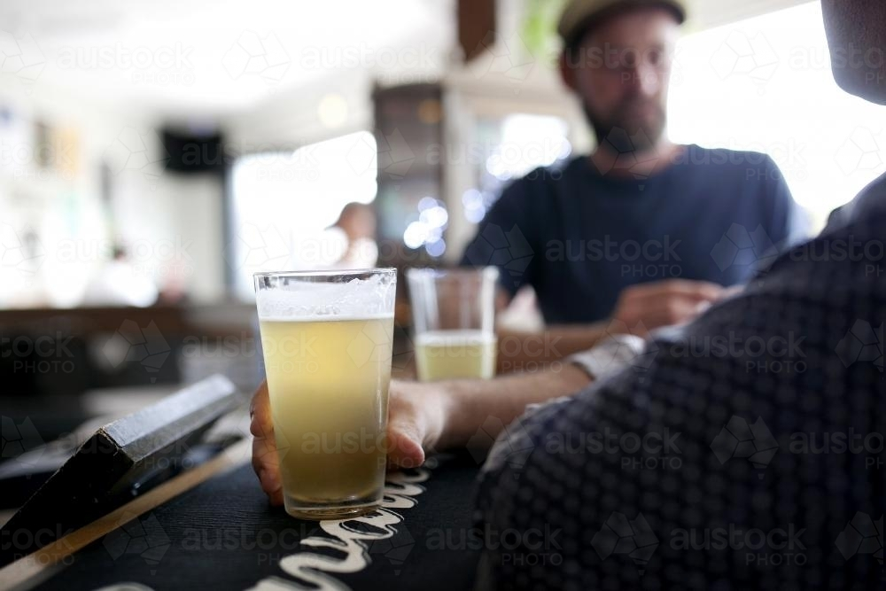 Men having a drink at the bar in a local craft beer pub - Australian Stock Image
