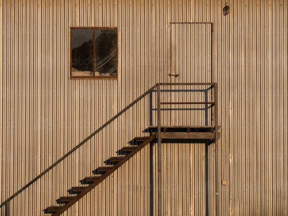 Metal steps on the side of a large corrugated building - Australian Stock Image
