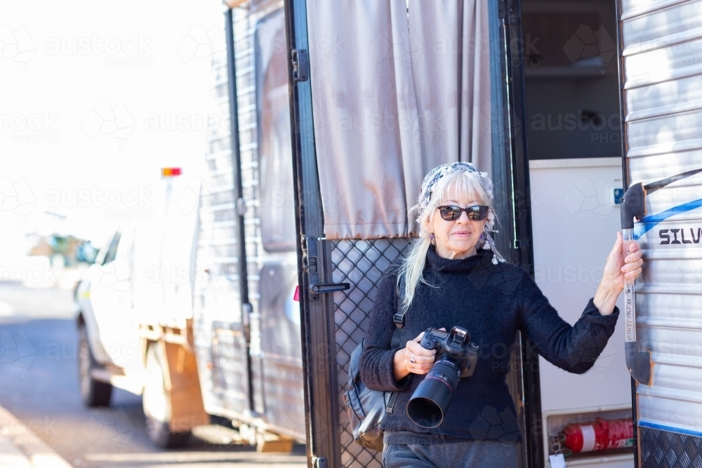 middle-aged lady traveller with camera at the caravan door - Australian Stock Image