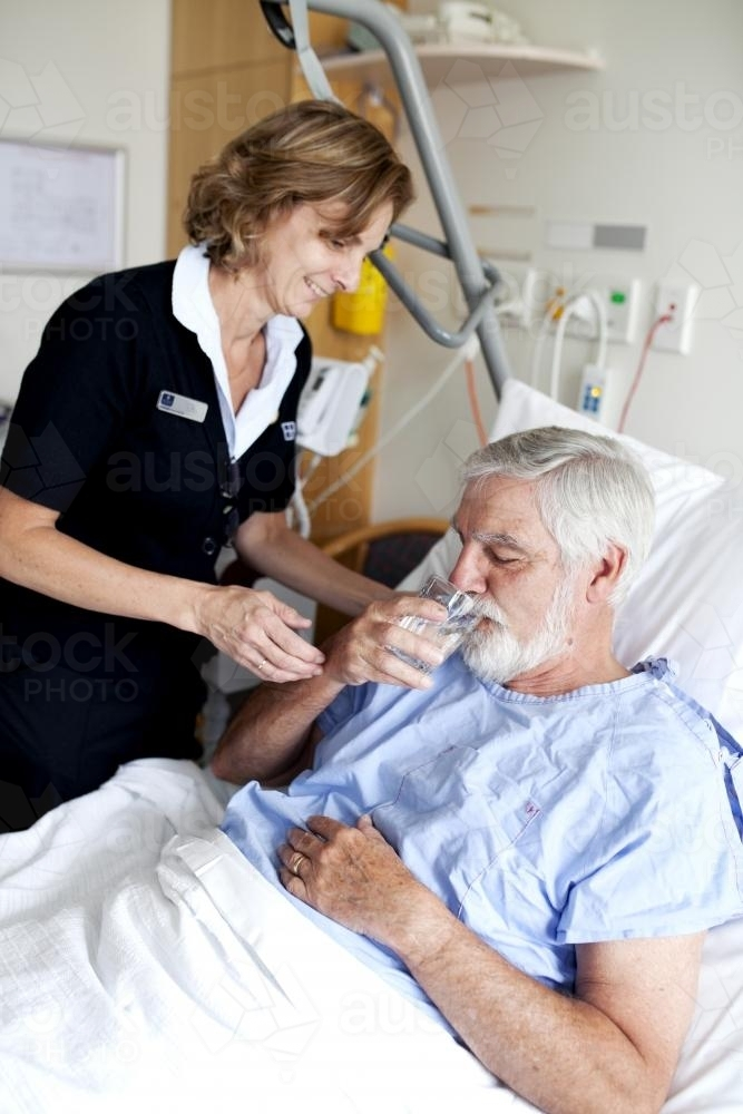 Middle aged male patient being given water by a nurse in a hospital ward - Australian Stock Image