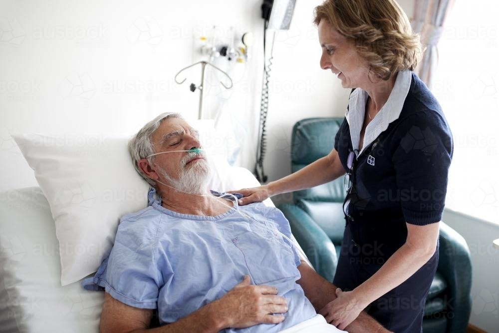 Middle aged male patient being treated by a nurse in a hospital ward - Australian Stock Image