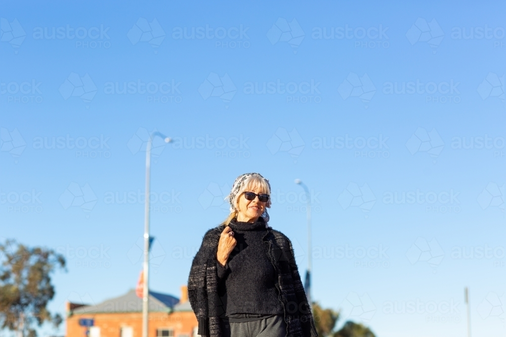 middle-aged woman wearing black against blue sky - Australian Stock Image