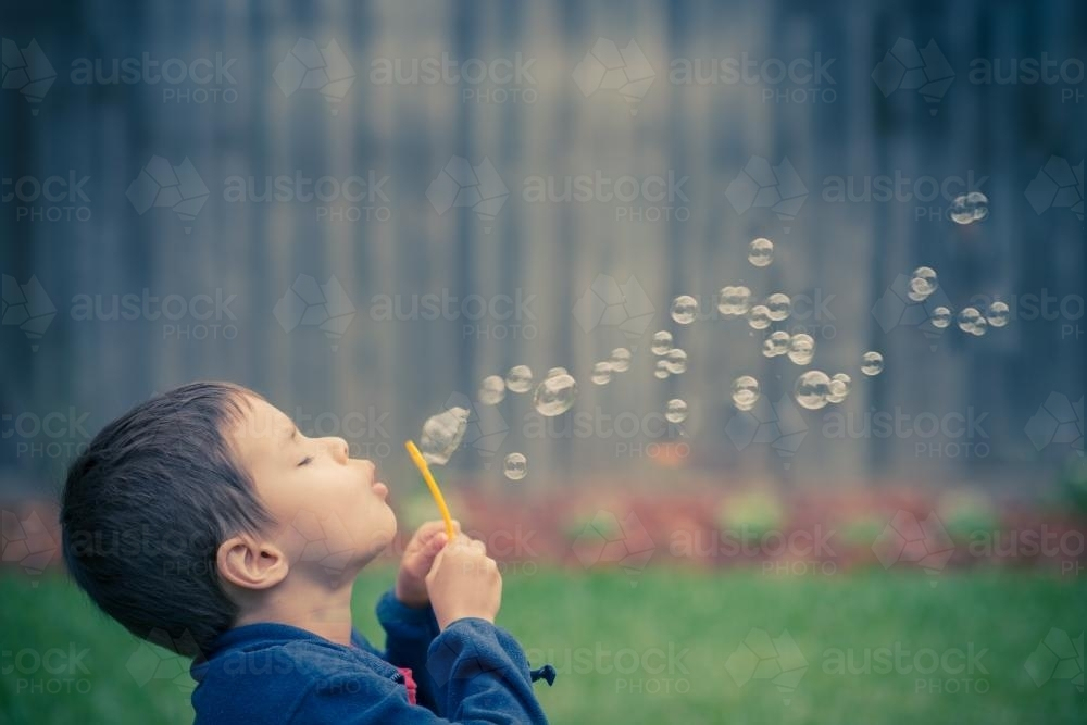 Mixed race boy blows bubbles in the yard of his suburban Sydney home - Australian Stock Image