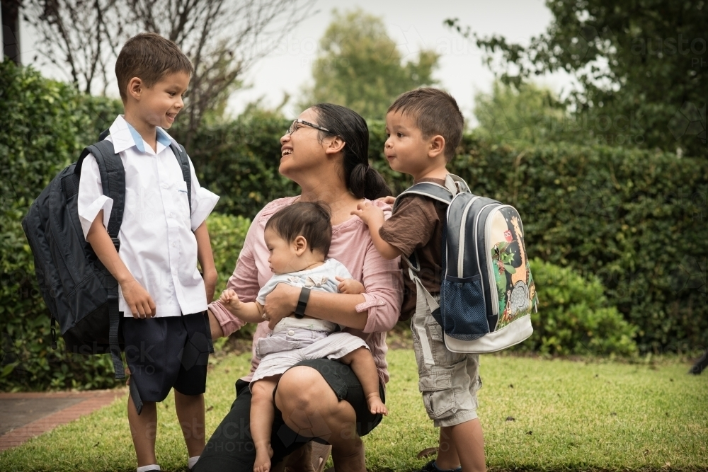 Mixed race boys say good-bye to their mum on their first day of school - Australian Stock Image