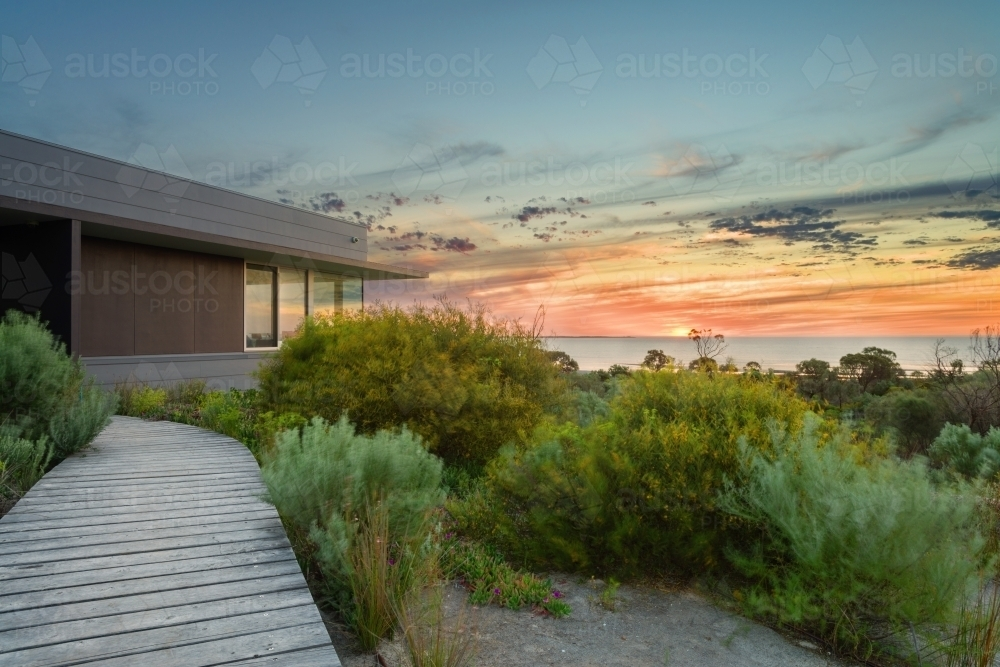 modern house overlooking the ocean at sunset - Australian Stock Image