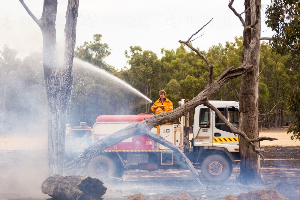 mopping up after a fire on a farm - Australian Stock Image