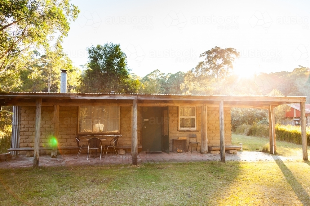 Morning sunlight flare over cottage in clearing - Australian Stock Image