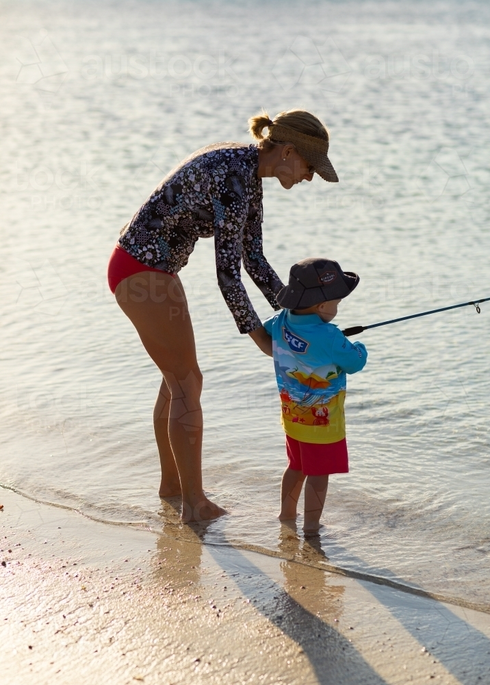 Mother and child fishing at the seashore backlit - Australian Stock Image