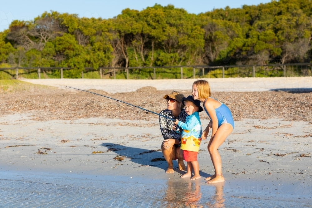 mother and children fishing on the beach - Australian Stock Image