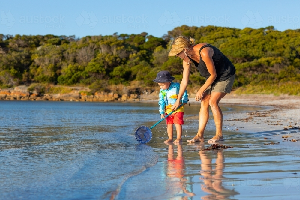 Mother and toddler with scoop net at the seashore - Australian Stock Image