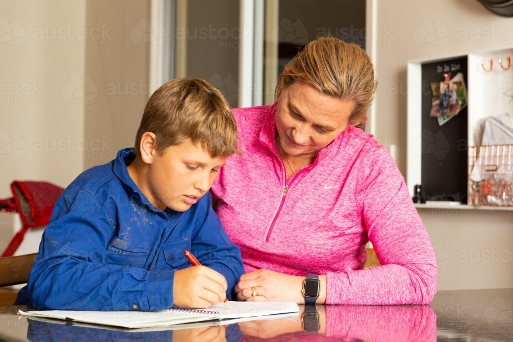 Mother helping child with homework - Australian Stock Image