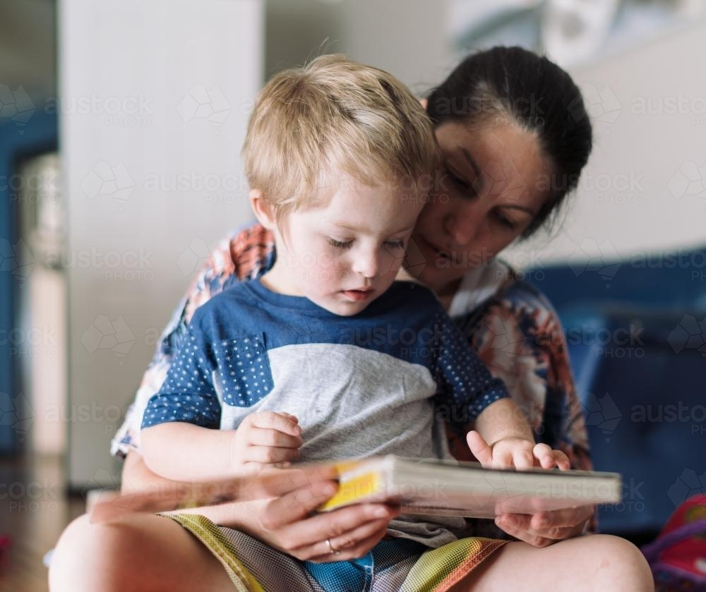 Mother reading to her child on the floor - Australian Stock Image