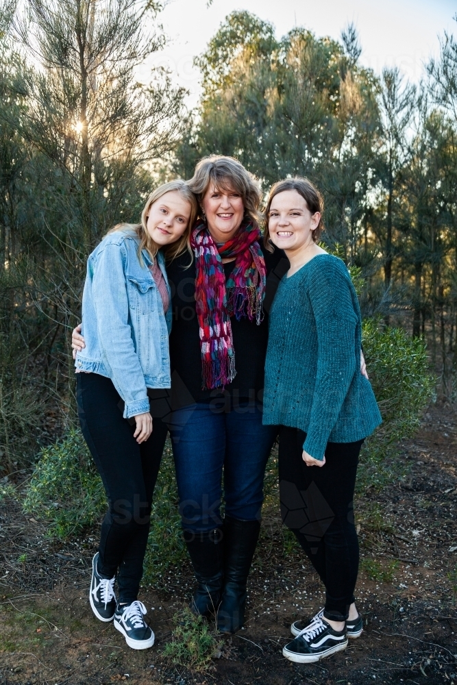 Mother with her two daughters hug together outside - Australian Stock Image
