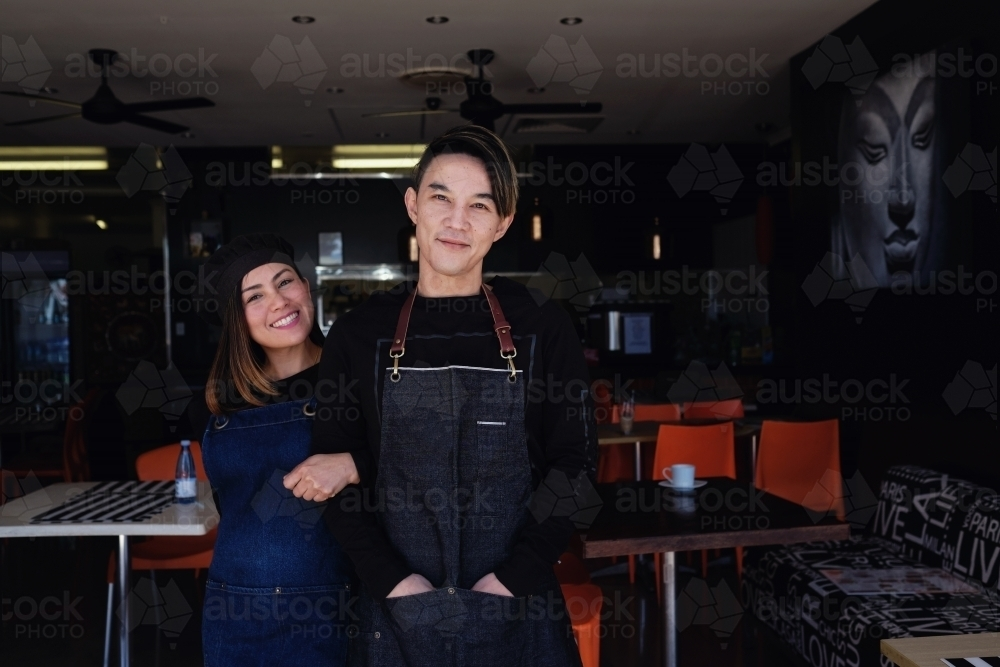 Multicultural Asian small business owners greeting in front of Thai restaurant - Australian Stock Image