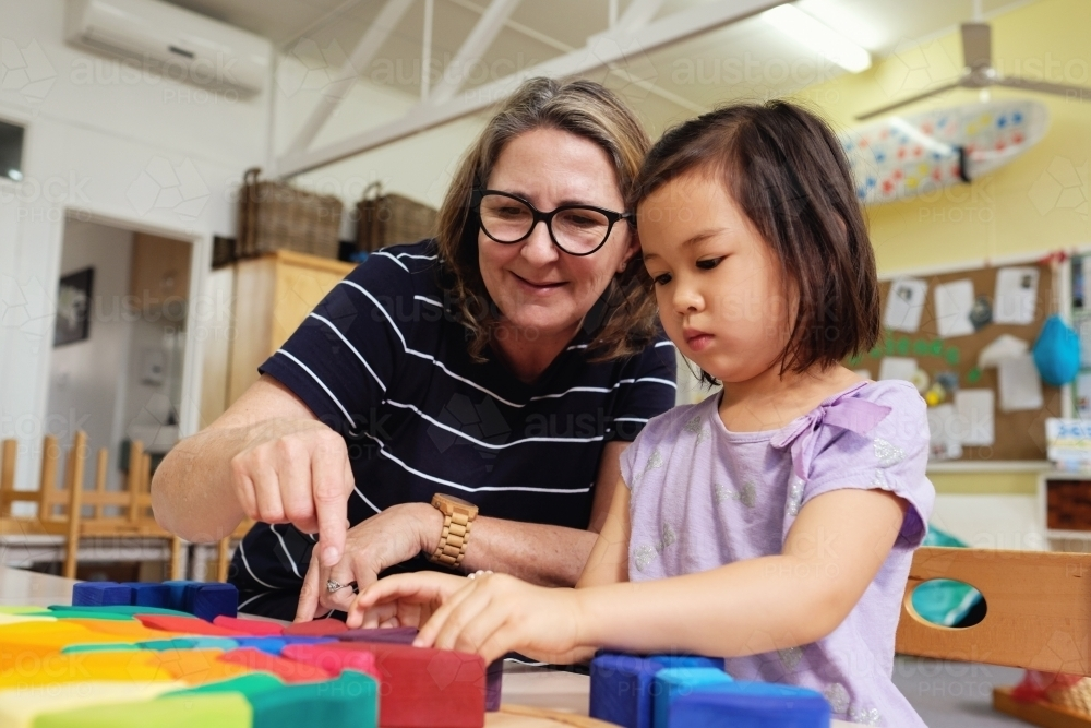 Multicultural teacher and child playing wooden blocks puzzles in kindergarten - Australian Stock Image