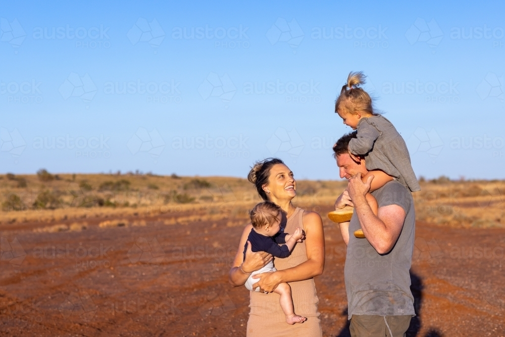 mum and dad with two little kids outdoors in the outback - Australian Stock Image