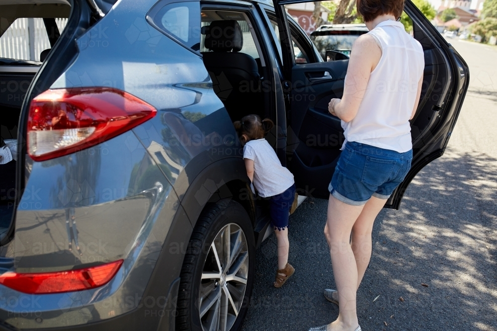 Mum and daughter getting in car - Australian Stock Image
