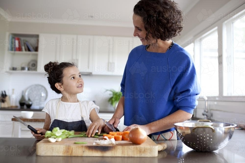 Mum and young girl chopping vegetables in kitchen - Australian Stock Image