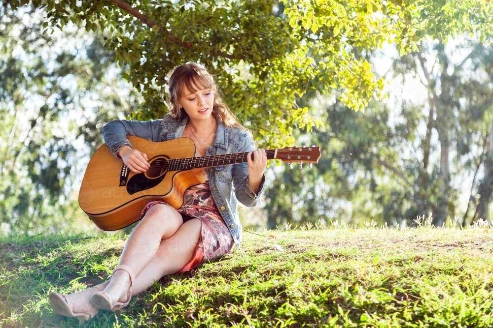 Musician sitting on a hill outside playing guitar - Australian Stock Image