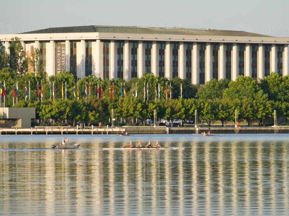National Library, Canberra, reflected in Lake Burley Griffin with rowers - Australian Stock Image
