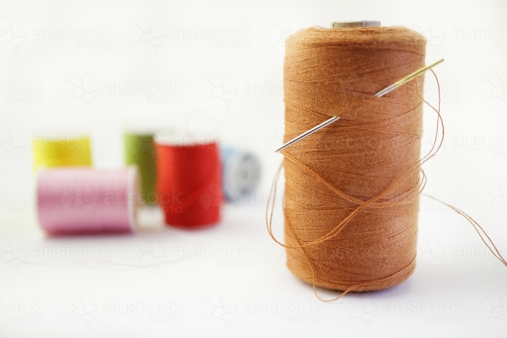 needle and thread with more cotton reels behind - Australian Stock Image