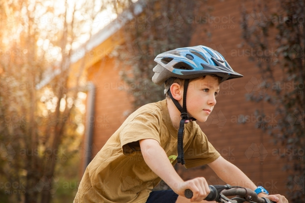 Nine year old boy riding his bicycle at home with helmet on - Australian Stock Image