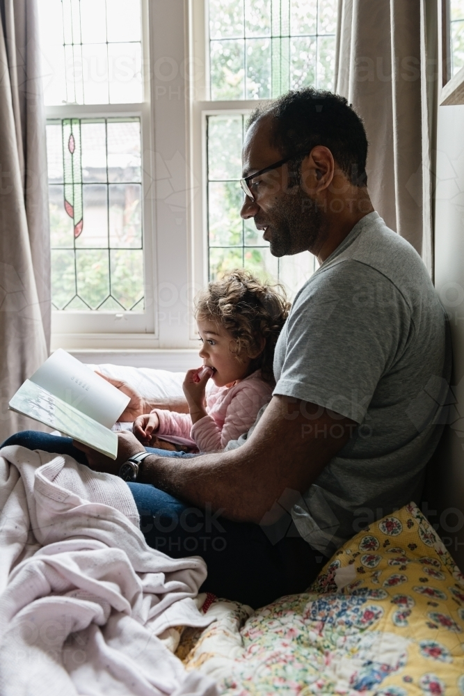 Daddy and little girl story time - Australian Stock Image