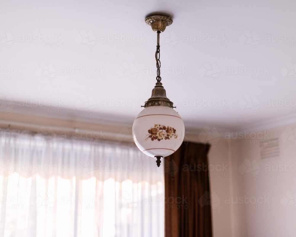 Old fashioned ceiling light hanging in a bedroom - Australian Stock Image