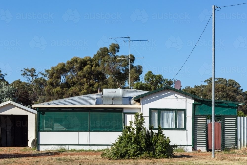 Old fibre house in front of trees - Australian Stock Image