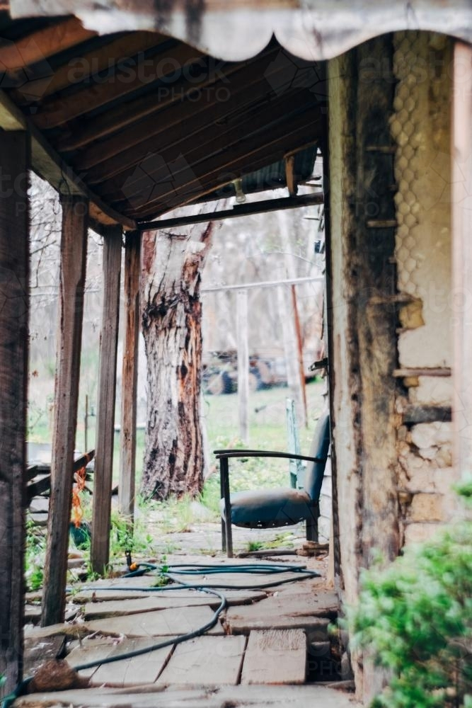 Old lounge chair on porch of rustic bush property - Australian Stock Image
