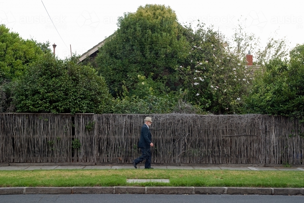Old man wearing a suit and hat walking down the street in front of a thatched wall